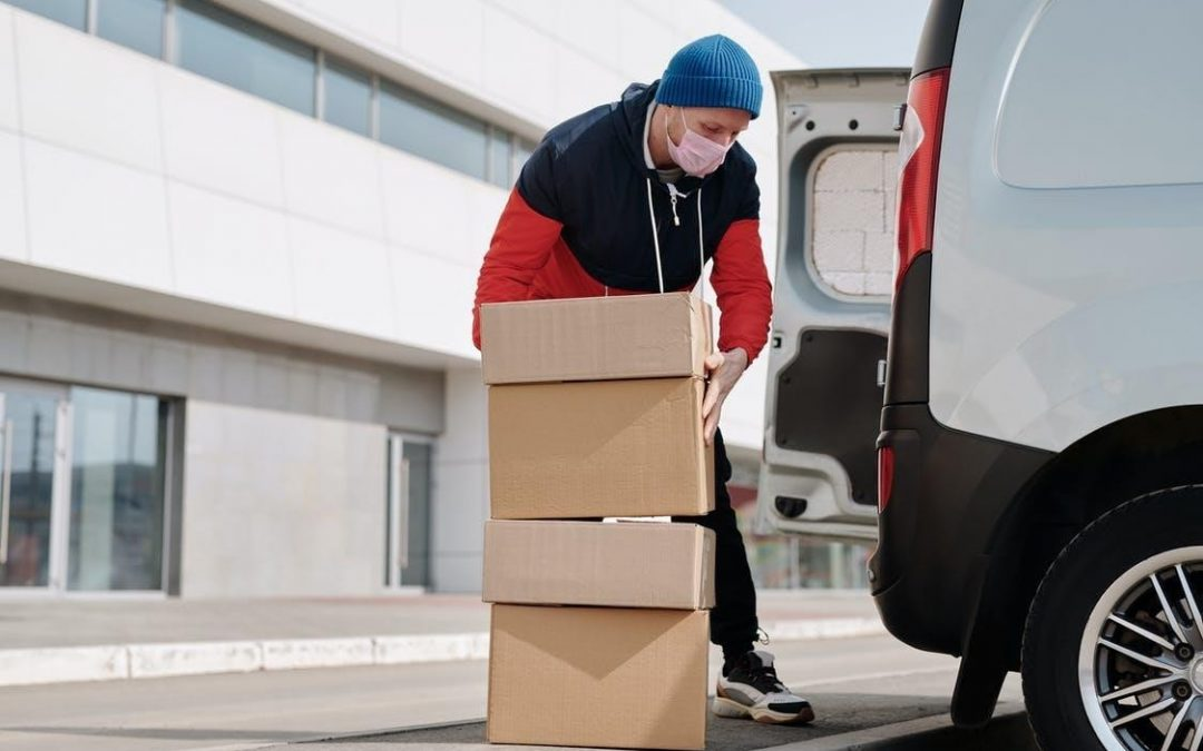 A delivery man unloading boxes from his van