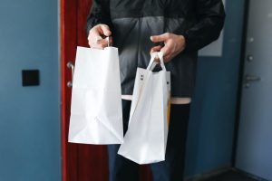A man holding two delivery packets received from an errand service provider.