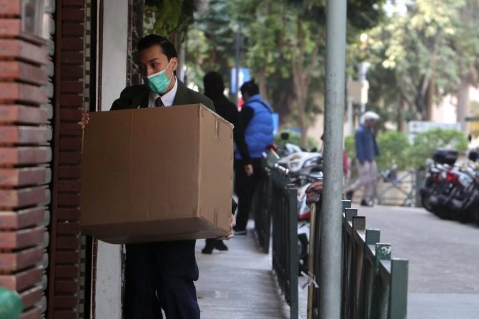 A man delivering a package while wearing a mask