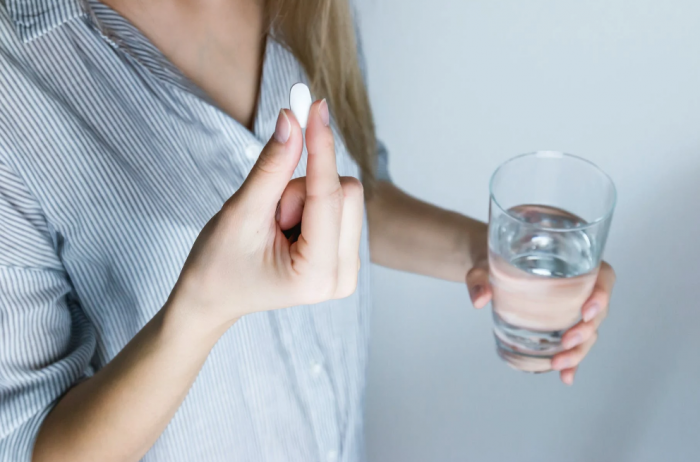 A woman is holding a pill from a medical courier service in San Angelo and a glass of water